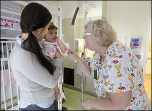 Toledo Hospital nurse Pattye Nicolls, right, greets Ayla Soria, 1, while she is with her mother Angalina Soria in the Debbie Brass Children's Cancer Center earlier this month.
