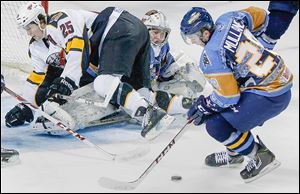 Cincinnati's Paul Crowder falls on Walleye goalie Hannu Toivonen as Pat Mullane takes control of the puck.