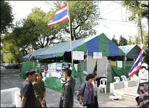 Thai anti-government protesters chat outside a makeshift camp where their colleagues were shot outside the prime minister's office of Government House on Saturday in Bangkok, Thailand.