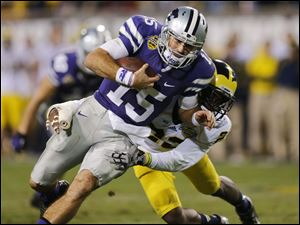 Kansas State quarterback Jake Waters (15) picks up the first down as he is tackled by Michigan safety Jarrod Wilson.