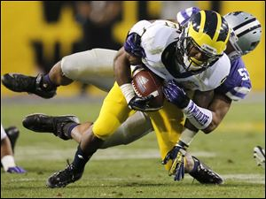 Michigan wide receiver Dennis Norfleet, front, is tackled by Kansas State linebacker Blake Slaughter.