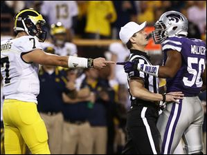 Michigan quarterback Shane Morris and Kansas State linebacker Tre Walker separated by official Land Clark during the second quarter.