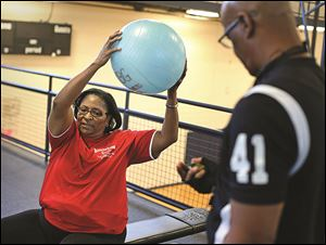 Karen Wright, left, does low-impact exercises under the supervision of personal trainer Harry Wright.