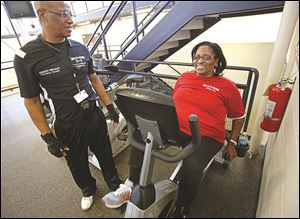 Karen Wright, right, works out on a stationary bicycle. She has heart disease and now uses a left ventricle assist device or HeartMate to help pump her blood.
