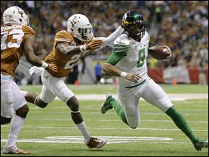 Oregon's Marcus Mariota (8) is chased by Texas' Mykkele Thompson (2) during the first quarter in the Valero Alamo Bowl.