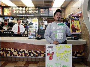 Protestor Juan Navarro demonstrates in front of the counter at a McDonald's restaurant on Dec. 5 in Los Angeles. Demonstrations were planned nation-wide as a part of push by labor unions, worker advocacy groups and Democrats to raise the federal minimum wage of $7.25 to $15.