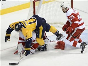Nashville Predators forward Nick Spaling (13) falls over Detroit Red Wings goalie Jimmy Howard after stopping a shot by Spaling while being defended by Red Wings defenseman Brian Lashoff (23) in the second period.
