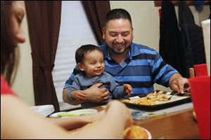 Rojelio Sanchez feeds his son Rojelio III, 2, with his daughter Karina, 18, at the family's home in Napoleon. Since being released from prison in 2011, Sanchez has made it his goal to provide a better life for his family.