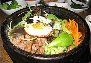 Korea Na's delicious bowl of dolsot bibim bap, a hot stone bowl full of rice, veggies, and a protein, is topped with an egg.