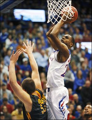 Kansas guard Andrew Wiggins, right, shoots over Toledo center Nathan Boothe, left, during the first half.