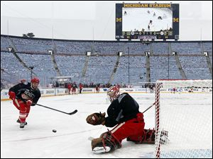 Detroit Red Wings defenseman Brian Lashoff , left, shoots on goalie Jimmy Howard during Tuesday's practice for the Winter Classic, the NHL's annual New Year's Day hockey game, in Ann Arbor. It's one of six outdoor games the NHL will host this season.