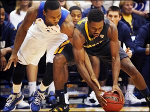 Kansas guard Wayne Selden, left, and Toledo guard Justin Drummond, right, battle for the ball during the first half of an NCAA colle