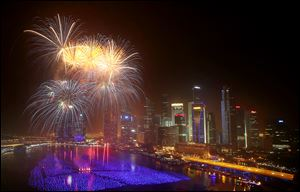 Fireworks explode over the financial district at midnight, Wednesday in Singapore. Celebrations started on New Year's Eve where concerts were held and thousands gathered on the streets to usher in the Year 2014.