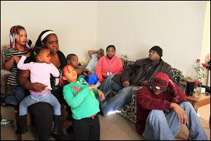 The slaying of Shawn Flowers, 22, is discussed by his sister, Donna Flowers, left, her daughter Alayla, 5; granddaughter ZaNaya, 7, and daughter ZyKeirra, 7. On the couch is Brandon Flowers, 26, and his wife, S'Neta, and the siblings' grandmother, Hazel Daniels. Brandon's son, KiViyan, 8, is facing him.  Seated on the floor is Brandon's brother, Ryan, 24. Shawn's Sept. 25 slaying was one of 31 in Toledo last year and one of 14 that remains unsolved. Police investigators say they have little information to go on to solve his homicide. Ryan Flowers says somebody knows what happened, but people either don't care or they are afraid to say anything for fear