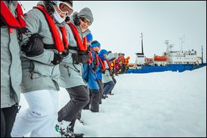Passengers from the Russian ship MV Akademik Shokalskiy link arms and stamp out a helicopter landing site on the ice near the trapped ship 1,500 nautical miles south of Hobart, Australia.