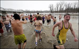 Hundreds of people join in the annual 'Polar Plunge' into the Maumee River on New Year's Day at Waterville Memorial Park.