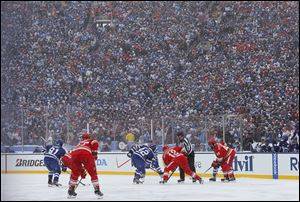 The Maple Leafs and the Red Wings face off during the first period of the Winter Classic in front of a reported 105,491 fans.