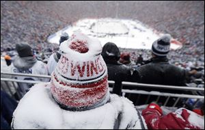 A Red Wings fan, coated with snow, watches during the third period. The Red Wings scored with less than six minutes remaining to force overtime, but lost in the shootout, 3-2.