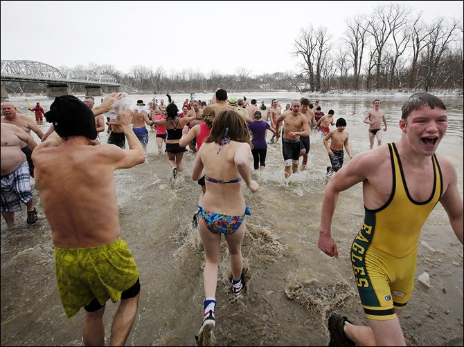 n5plunge-3 Hundreds of people join in the annual 'Polar Plunge' into the Maumee River on New Year's Day at Waterville Memorial Park.