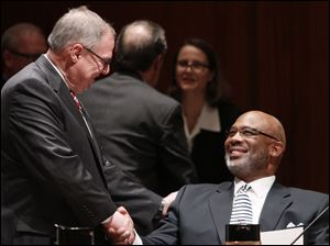 New Toledo Mayor D. Michael Collins shakes hands with new councilman Larry Sykes.