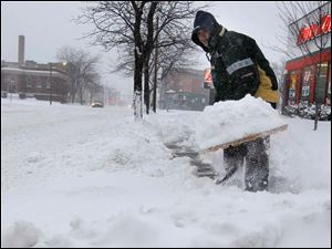 Auto Zone worker Juan DeLatorre shovels the sidewalk of Auto Zone on Broadway.