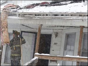 Icicles formed by water from a fire hose hang from the gutter of an occupied home that caught fire on Parker Avenue.