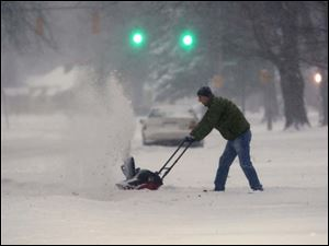 Toledoan Jason Huther snow blows his driveway on Heatherdowns Boulevard.