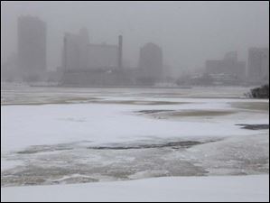 The Maumee River is frozen over and downtown Toledo is shrouded in blowing snow.