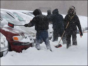 Mo Tawil, right, is among a dozen workers shoveling snow off of about 900 cars at Nationwide Auto on Woodville Road.