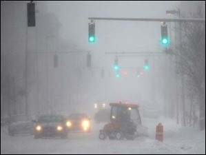 A snowplow clears sidewalks on Adams Street.