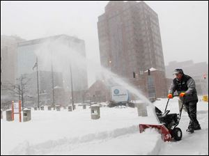 Imagination Station facility worker Robert Rising snow blows the entrance of the science center during a snow storm in downtown Toledo. Because of the heavy snowfall, Imagination Station closed for the day.