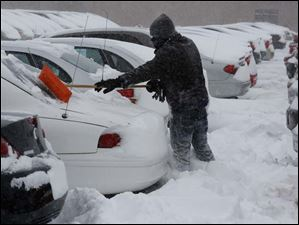 Terry Cox shovels snow off a vehicle at Nationwide Auto Finance.