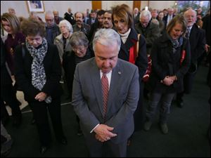 George Sarantou is in front of the crowd during the prayer before D. Michael Collins takes the Oath of Office for the Mayor of Toledo in the lobby of One Government Center on Thursday.