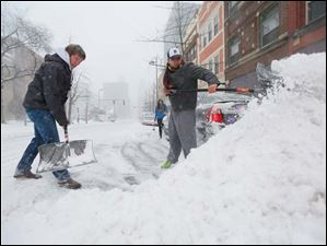 Brad Anderson, left, and Justin Guerrero, right, shovel out their car that is stuck on Madison Street in downtown Toledo.