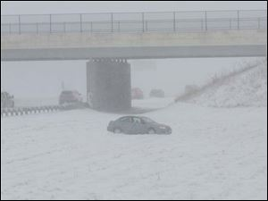 A car sits alone after sliding off of I-75 South near the US 23 exit during a level 2 Snow Emergency in Lucas County.