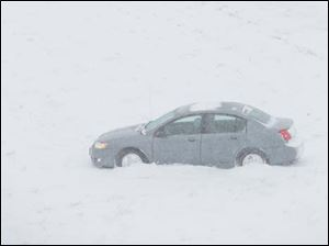 A car is idle after sliding off of I-75 South near the US 23 exit during a level 2 Snow Emergency in Lucas County.
