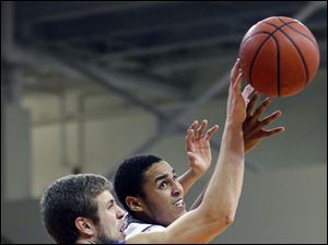 IPFW  forward Joe Reed (44) knocks the ball away from Bowling Green State University center Josh Gomez (0).