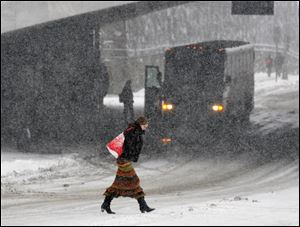 Marianne Stewart, of Albany, crosses Madison Ave. as snow rocks the East Coast.