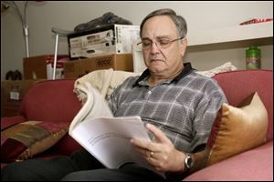 Howard Kraft looks over healthcare information in his Lincolnton, N.C. home Monday. A painful spinal problem left him unable to work as a hotel bellman. But he's got coverage because federal law now forbids insurers from turning away people with health problems.