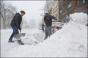 Brad Anderson, left, and Justin Guerrero shovel out their car, stuck on Madison Avenue on Thursday. The scene was a familiar one for many motorists.