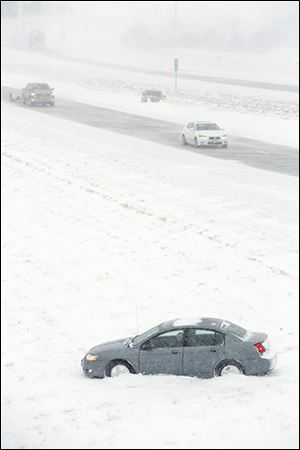 A car sits idle after sliding off  I-75 southbound near the U.S. 23 exit during the  snow storm Thursday.