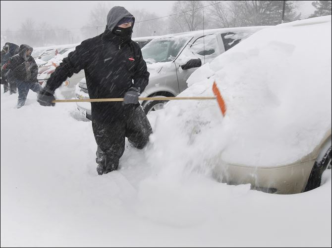 30n6shovel Al Tawil, owner of Nationwide Auto Finance, joins 12 workers shoveling snow off 900 cars in the lot as snow continues to fall at the business on Woodville Road in Oregon.