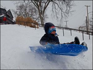 Benjamin Kuhlman, 5, hits a jump while sledding near Harvard School in South Toledo.