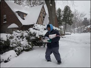 Postal carrier Nick Fitzgerald treks through the snow while making his deliveries in West Toledo.