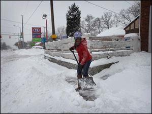 Treona Smith, 16, clears snow from the sidewalk in front of her home Thursday in West Toledo.