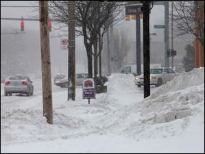 Businesses along Secor Road had carrying degrees of cleared sidewalk Thursday.