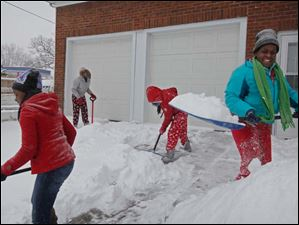 Sisters Treona Smith, 16, left, Sierra, 14, center left, Lachelle, 12, center right, and their cousin Latara Walker, 12, right, clear snow from the sidewalk and driveway at the Smiths' home Thursday.
