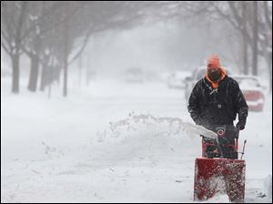 Don Haubert blows snow around the edge of his driveway Thursday on Hayes Avenue in Fremont.