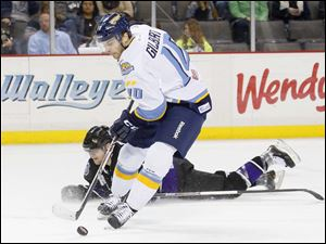 Toledo Walleye player David Gilbert (10) knocks down Reading Royals player Marvin Degon (4) as he skates the puck in during the first period.