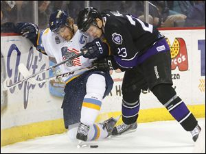 Toledo Walleye player Kyle Rogers (17) and Reading Royals player Bryant Molle (23) battle for the puck during the first period.
